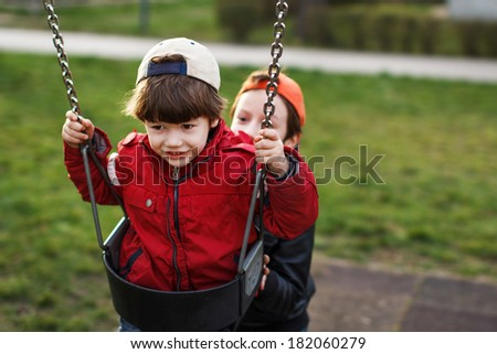 Little boy swinging, brother help, outdoor portrait - stock photo