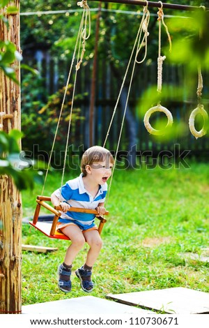 little boy swinging on the swings and shouts of joy