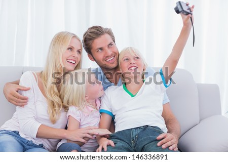 Little boy taking pictures of his family in the living room