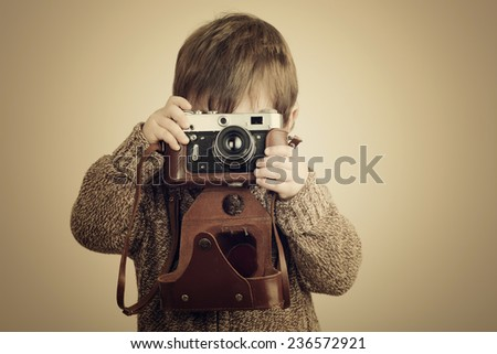 little boy taking pictures with old camera - stock photo
