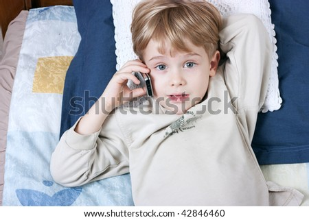 Little boy talking by mobile phone - stock photo