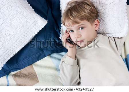 Little boy talking by mobile phone very emotional - stock photo