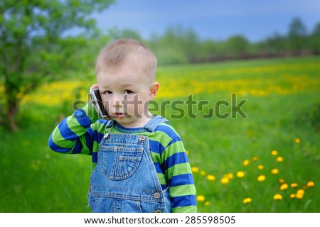 little boy talking on the phone on a spring meadow. - stock photo