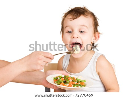 Little boy tasting vegetable salad
