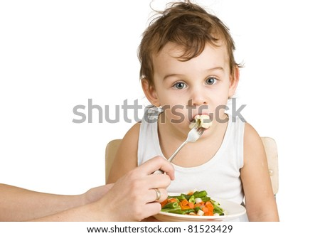 Little boy tasting vegetable salad - stock photo