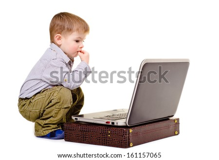 Little boy thoughtfully sits at a notebook - stock photo