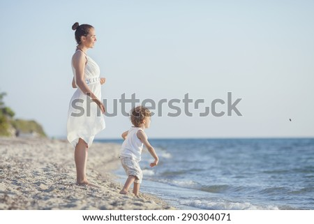 Little boy throwing pebbles to the sea while his mother is waiting him - stock photo