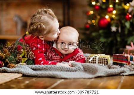 Little boy toddler in a red sweater kisses his older sister, lying together on a cozy blanket on the Christmas tree and garlands in the house next to the gifts - stock photo
