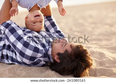 Little boy toddler laughing as his dad is playing by turning him upside down - stock photo