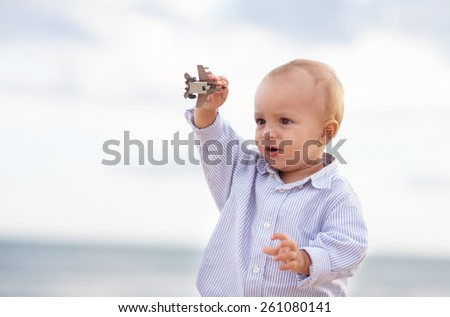 Little boy toddler playing with a toy plane, outdoors with sky in the background - stock photo