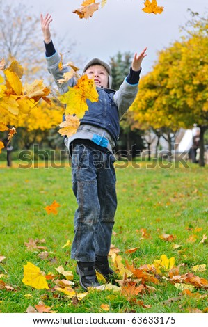 Little boy   tossing up yellow leaves - stock photo
