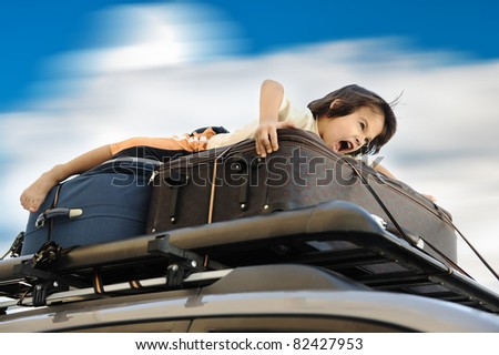 Little boy traveling on the top of the car - stock photo