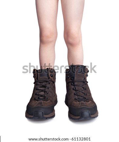 Little boy trying his father's hiking shoes isolated on white - stock photo