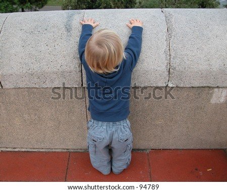 Little boy trying to climb a low wall - stock photo