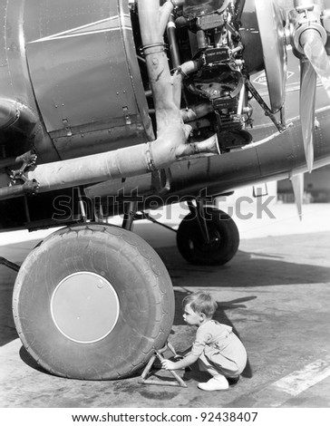Little boy trying to fix an airplane wheel - stock photo