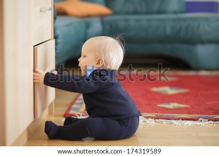 Little boy trying to open and look inside drawer chest. - stock photo