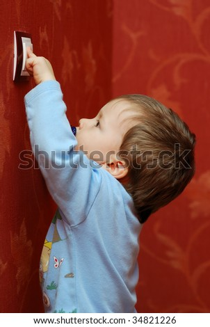little boy turning off the light-switch - stock photo