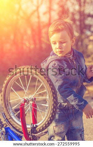 Little boy turning the wheel on his bike on the background of the sun's rays. natural composition - stock photo