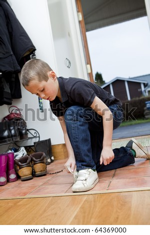 Little Boy tying his shoes before he gets outdoor - stock photo
