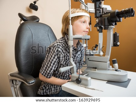 Little boy undergoing eye examination with slit lamp in store - stock photo