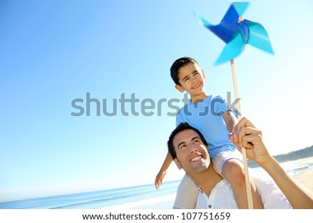 Little boy up on his fathers's shoulders holding swirl - stock photo