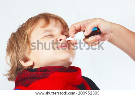 Little boy used a medical nasal spray in the nose on a white background