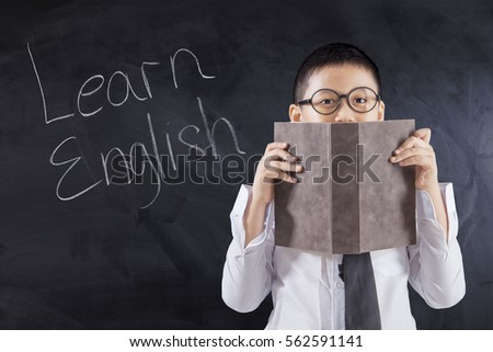 Little boy using a book to cover his face with text Learn English on the blackboard, shot in the class