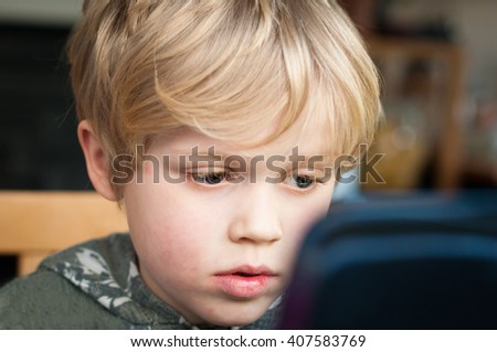 Little boy using a laptop to browse the internet - stock photo