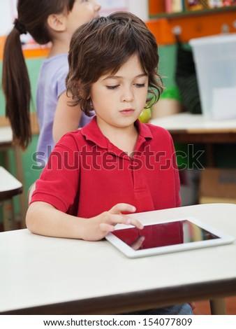 Little boy using digital at desk with friend in background at kindergarten - stock photo