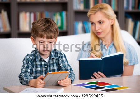 Little boy using tablet computer in psychologist office. Focus on boy. Psychologist making notes. There are many books in psychologist office - stock photo