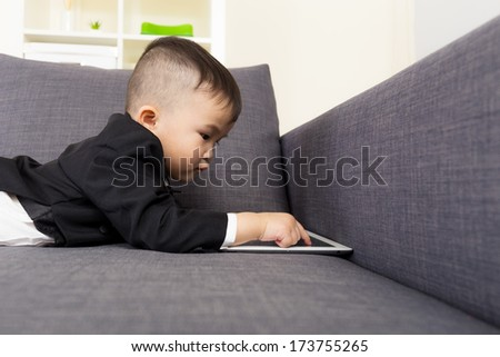 Little boy using tablet on sofa