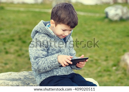 Little boy using tablet outdoor at spring or autumn - stock photo