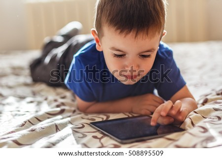 Little boy using tablet while lying on bed, natural light.