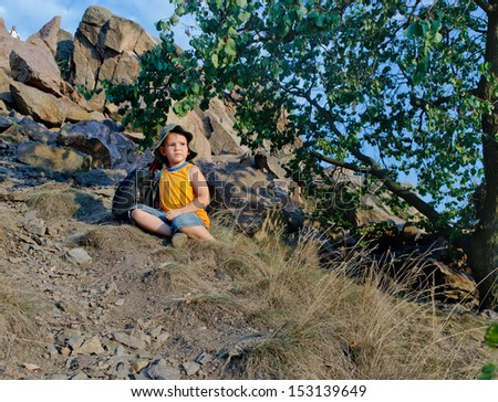 Little boy waiting patiently on a mountain slope alongside his backpack while his father rock climbs way up on the mountain peak in the distance - stock photo