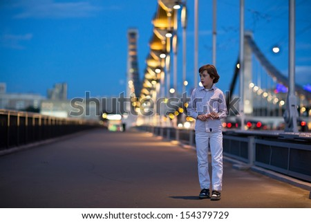 Little boy walking alone scared on a beautiful bridge in a dark city at night - stock photo