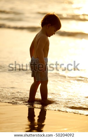 little boy walking along the beach during the sunset - stock photo