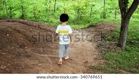 Little boy walking away in garden - stock photo