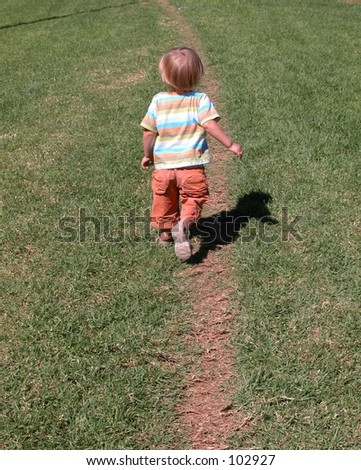 Little boy walking away on a path in the grass - stock photo