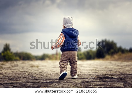 Little boy walking, picture from behind - stock photo