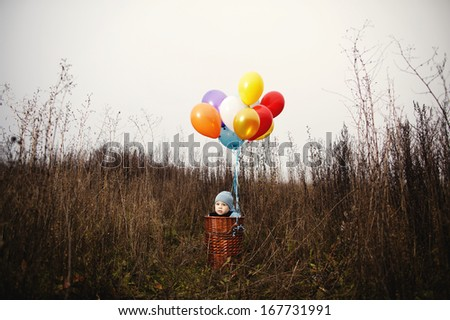 little boy wants to fly on balloons away - stock photo