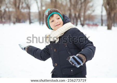 little boy wants to throw a snowball - stock photo