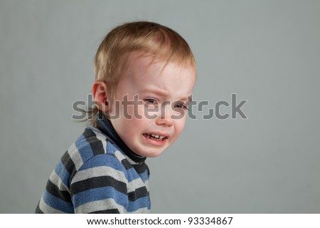 little boy was crying bitterly, and looks into the camera - stock photo