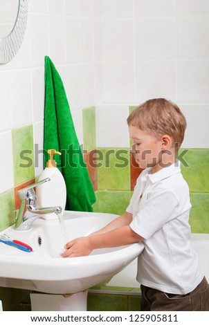 little boy washes in a bathroom