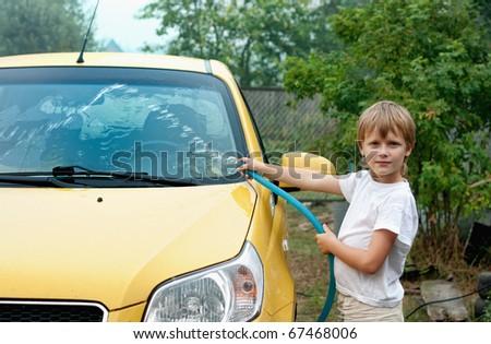 Little boy washing car - stock photo