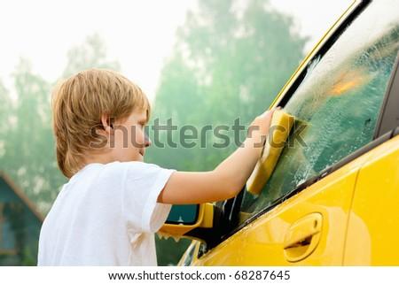 Little boy washing car. Summer. Sunset - stock photo