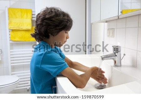 Little boy washing his hands in the bathroom - stock photo