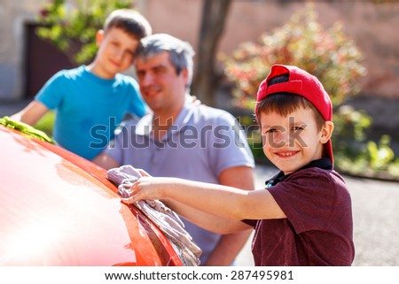 Little boy washing red car with family - stock photo