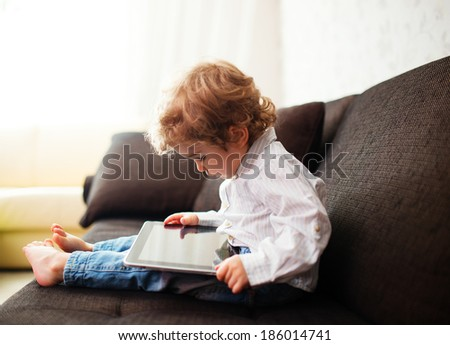 Little boy watching a movie on tablet, indoor  - stock photo