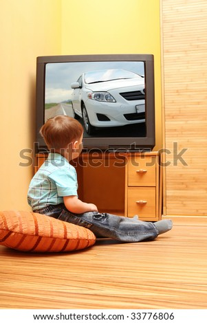 Little boy watching cinema on TV. TV screen - photo of the author - stock photo