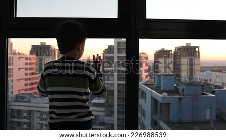 little boy watching sunset through the window  - stock photo